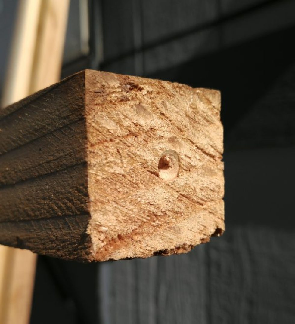 The end of a 2x2 wooden pole, with a small hole banged into the center of it. That's where the drill bit goes.