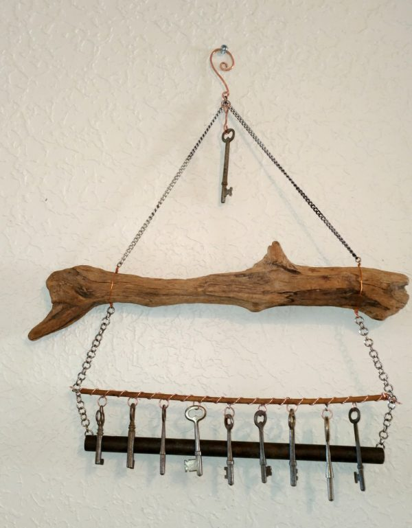 Instead of a chain, the keys are now hanging from a thin wooden dowel, which runs between the two chains that hold up the tube chime. The whole thing is hung from a hook on the wall.