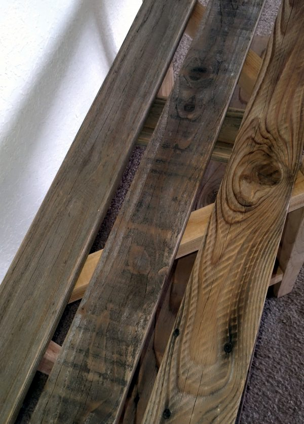 Three 1x3 boards, of old, weathered wood, lined up parallel to each other.