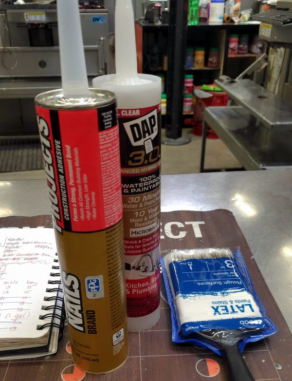 Still life on the paint counter: the notebook, a medium-cheap paintbrush, & two different kinds of caulk. That's C A U L K in case you were concerned.