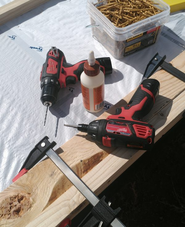 The same two boards, now with a pair of drills & a half gallon container of wood screws set nearby.
