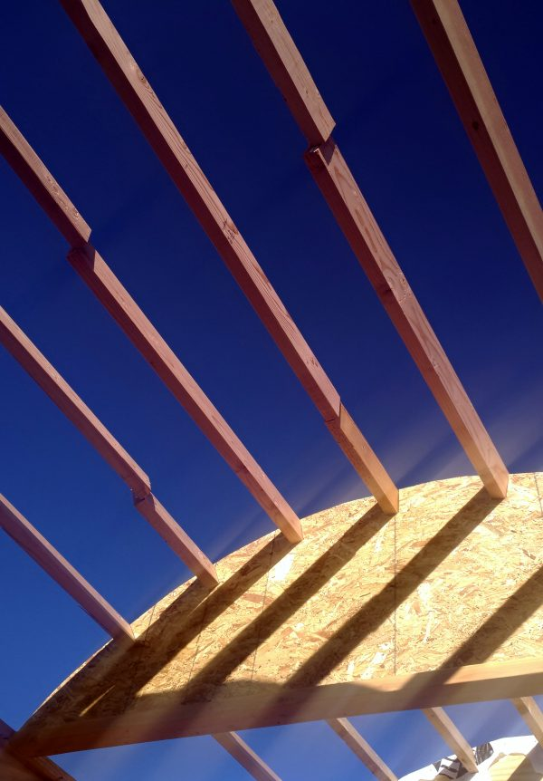 One of the center two roof arches, with a rafter set into each notch; above that are several parallel sets of rafters with deep blue sky above them.