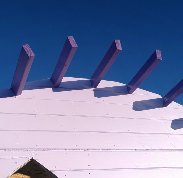 A view looking upward at an angle -- the top of the front wall, painted lavender; the exposed parts of the rafters, painted a deeper purple; & behind it all, that deep blue New Mexico sky.