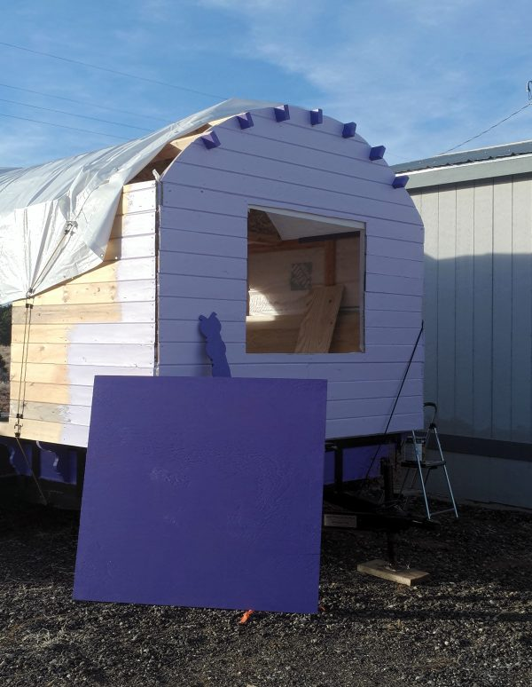 The back wall, now painted the same pale lavender as the front; the short exposed parts of the rafters are the same darker purple as the half-sheet of plywood leaning against the tinker's wagon.