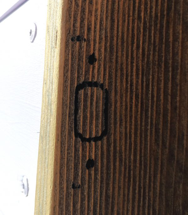 A bit of doorframe, upon which is drawn, in Sharpie, the rough outline of the strike plate. That's the metal bit around the hole where the latch goes.