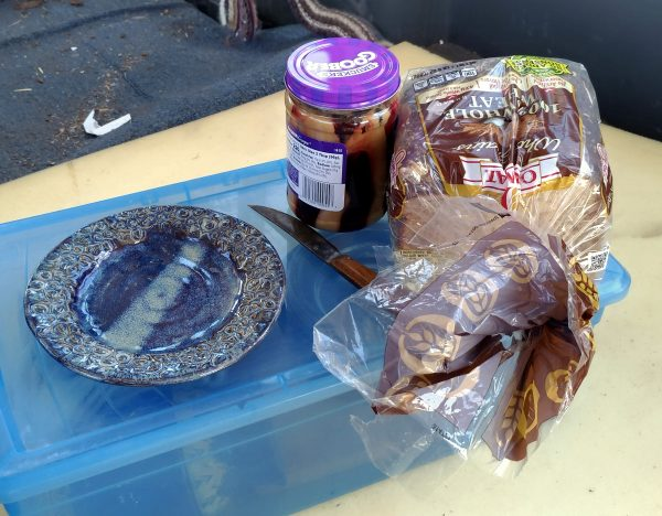 Inside the van, a plate, knife, loaf of bread, & jar of mixed peanut butter & jelly sit on a blue plastic box.