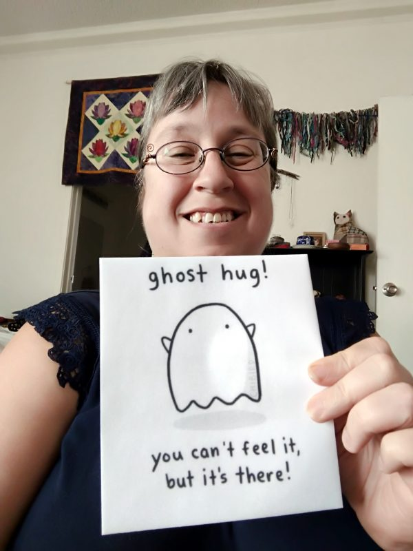 """Me, a white person with glasses & brown hair, smiling at the camera. I'm holding a sign that bears a simple drawing of a ghost & the words """"Ghost hug! You can't feel it, but it's there!"""""""
