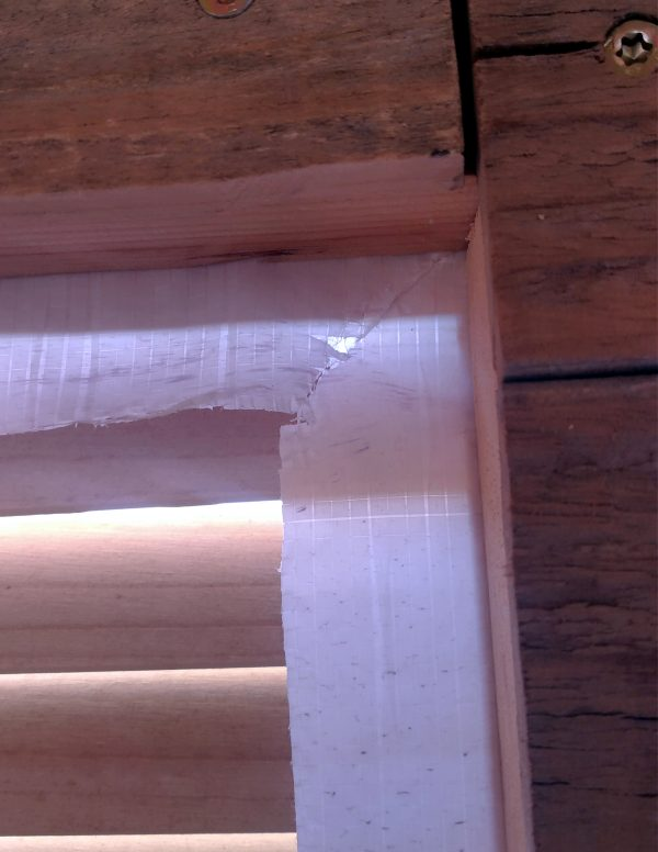 A corner of the window; the housewrap is cut diagonally out from the corner, so it can fold flat along the inside edge of the window.