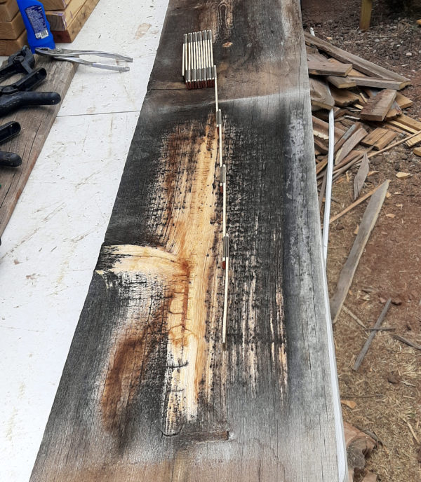 A rough wooden board lays on a table outside, with a folding ruler atop it. Th eboard is about a foot wide & several feet long; most of it is weathered to dark brough, but there's a pale streak down the middle, & a knot on the left side that's also pale.