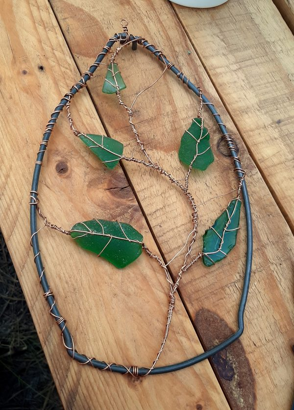 The mostly-finished piece. The bucket handle acts as a frame; it's broad at the bottom and narrows to a point at the top where the two ends are twined together. A long vine of copper winds its way up the middle, with five green sea glass leaves, wrapped in copper, emerging from it.