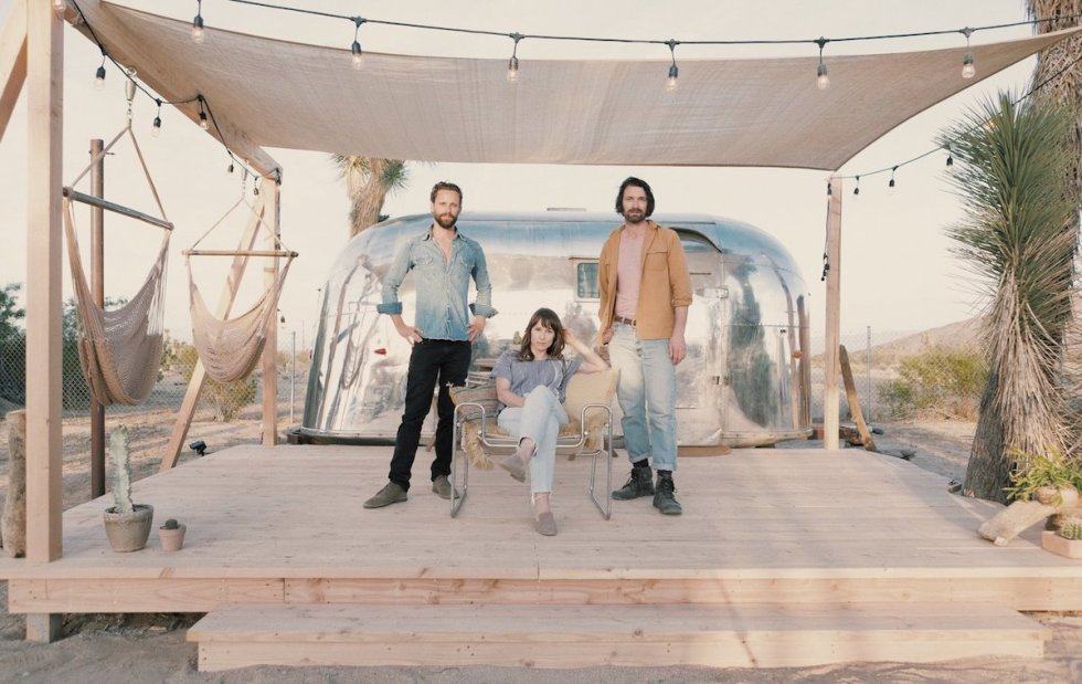 """Andrew Uhlhorn, Justine Bennett and Joseph August outside the """"1959 Kind of Blue"""" Airstream, Joshua Tree Acres, California, USA."""