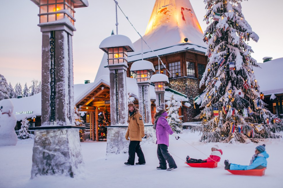 A family crossing the Arctic Circle in Santa Claus Village near Rovaniemi in Lapland, Finland.