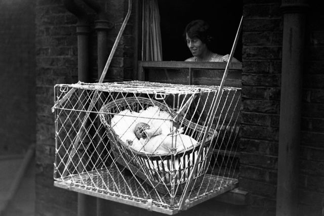 "Mother dangling a ""baby cage"" out of her apartment window"