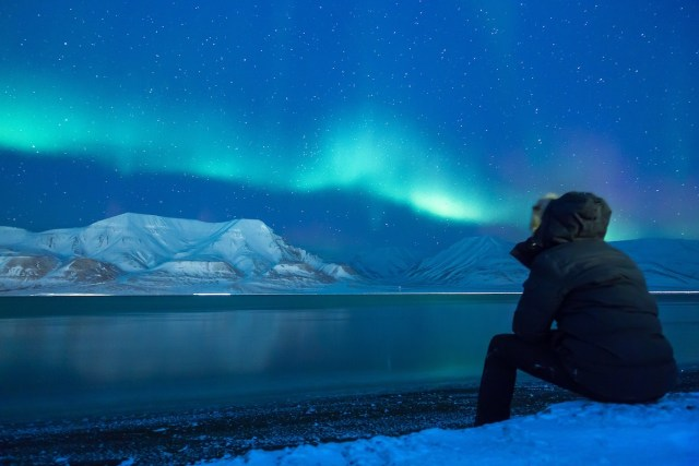 Man watching The Northern Lights in Longyearbyen, Norway.