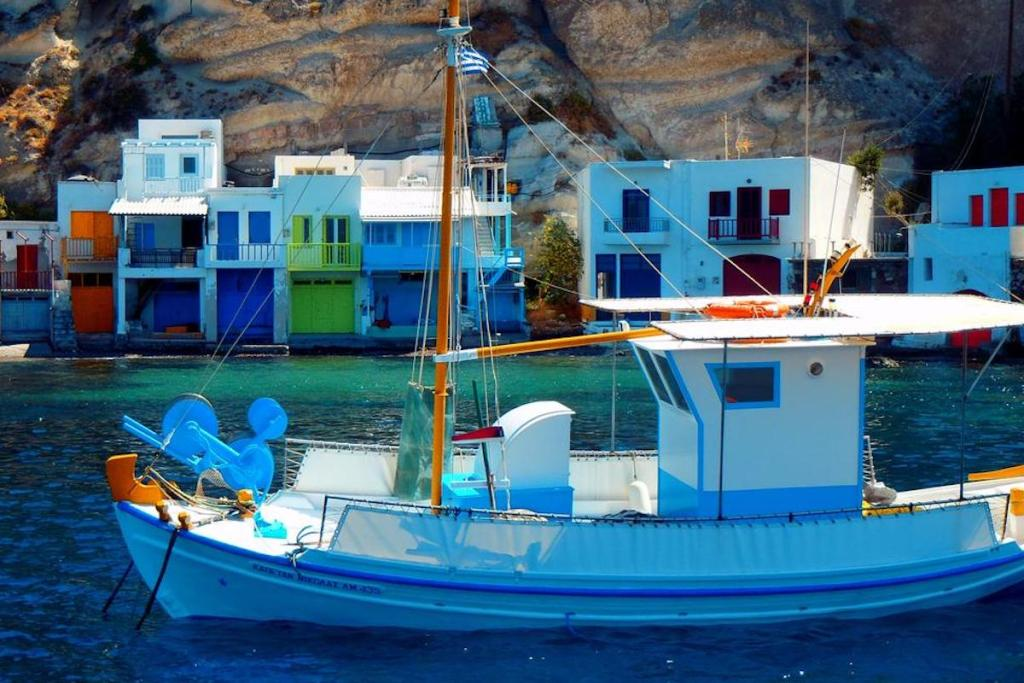 Fishermen houses with bright colored doors that are carved into the rocks at Klima Village in Milos, Greece.