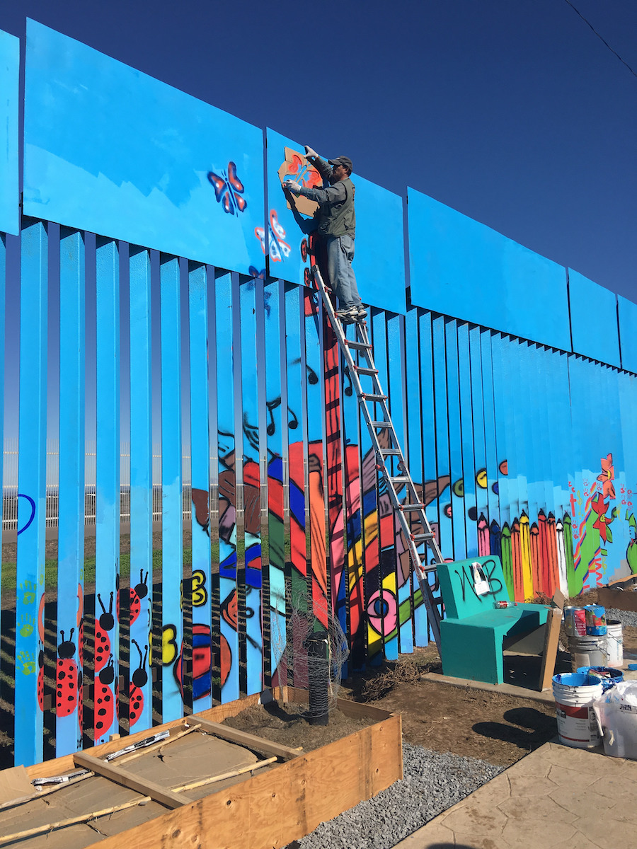 "Artist Enrique Chiu painting a section of his project, ""Mural of Brotherhood,"" on the US-Mexico border wall. Photo: Enrique Chiu"