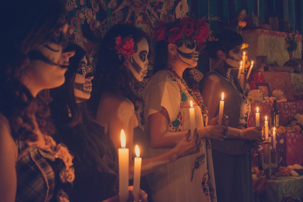 Women, dressed in fancy costumes and holding candles, stand next to an ofrenda