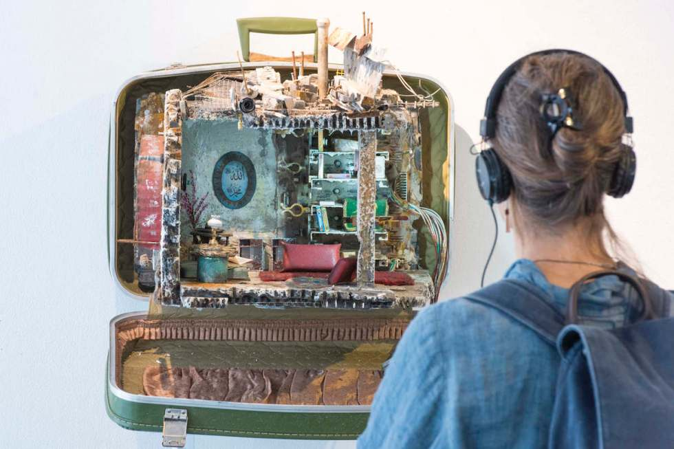 "Woman with headphones looking at an old suitcase from ""UNPACKED: Refugee Baggage"" installation"