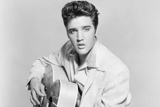 Elvis Presley posing for a photo while playing his guitar
