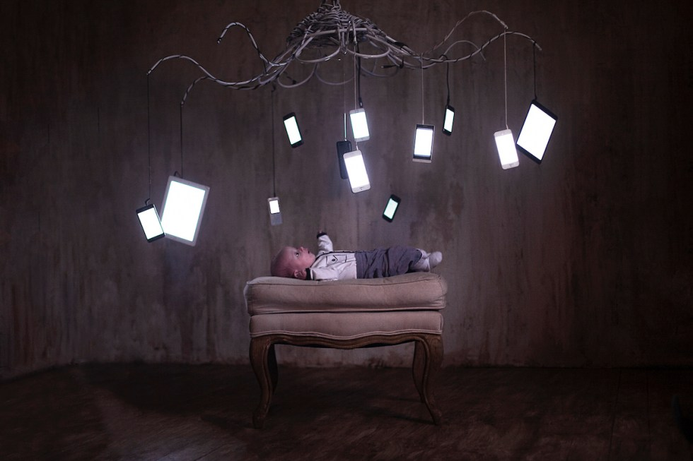 baby lying on a sofa bench surrounded by mobile internet devices