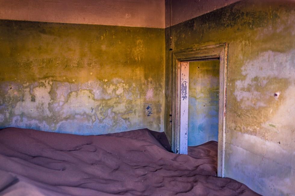 sand-filled room inside an abandoned home at Kolmanskop ghost town