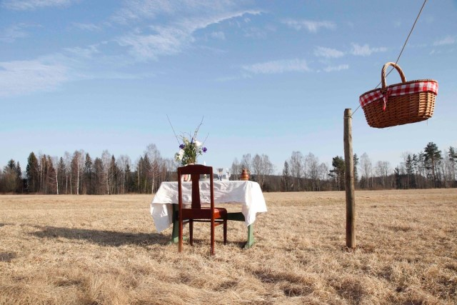 one table, one chair, and a picnic basket in the middle of a lush meadow