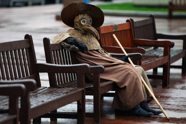 "a Glasgow-based artist dressed in a 17th-century Plague Doctor costume, sits on a bench in George Square in 2011 in Glasgow, Scotland, to promote his exhibition, ""The Human Condition"""