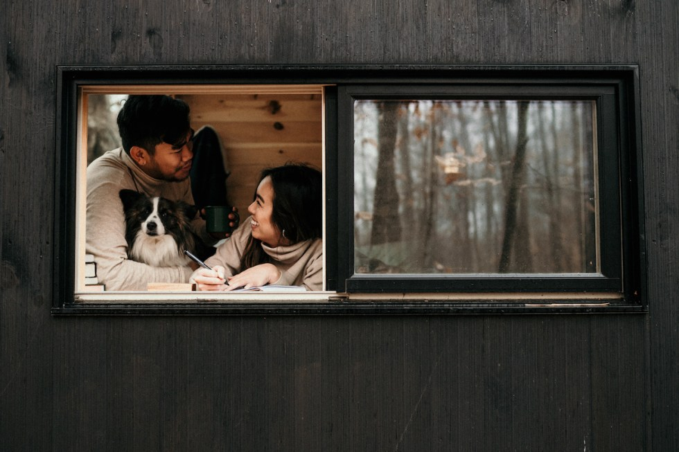 a young couple and a dog inside a cabin in the woods