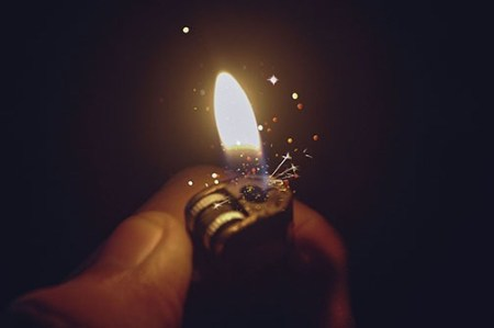 closeup of lighter flame with sparks illuminating static electricity that can be dangerous in hydrocarbon extraction