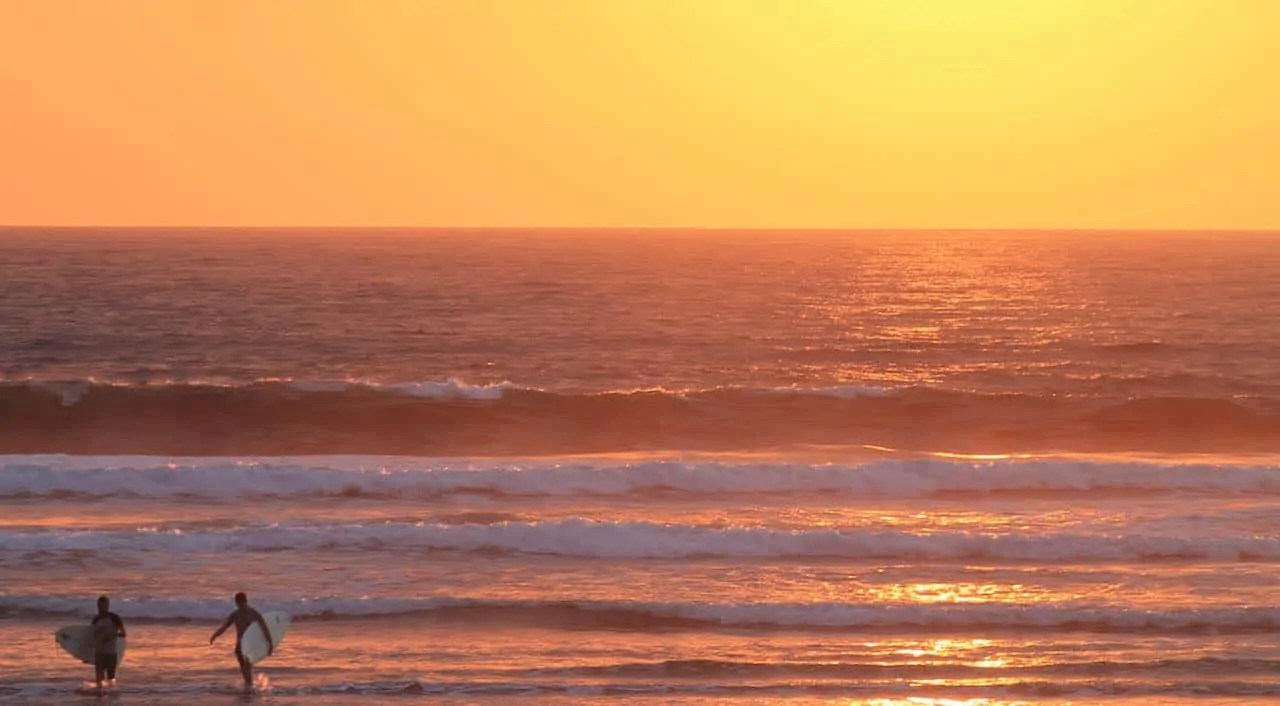 Two surfers walking back at sunset