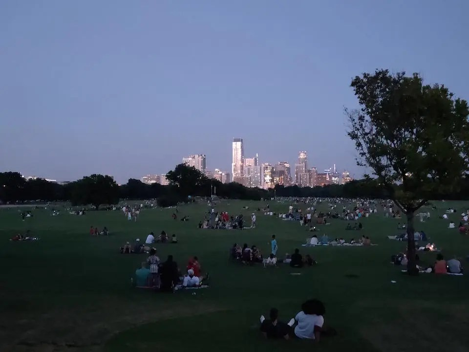 Large green park with downtown Austin light up at night in the background