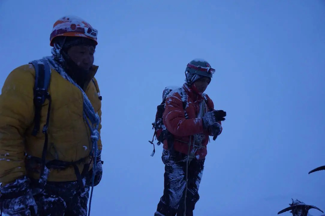 Two guides against the white snow on the summit of Huayna Potosi
