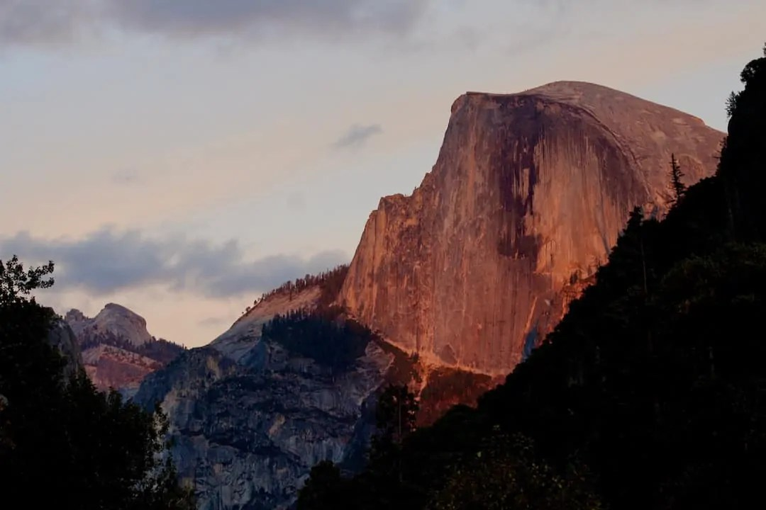 The sun casting a yellow glow on Half Dome in Yosemite National Park