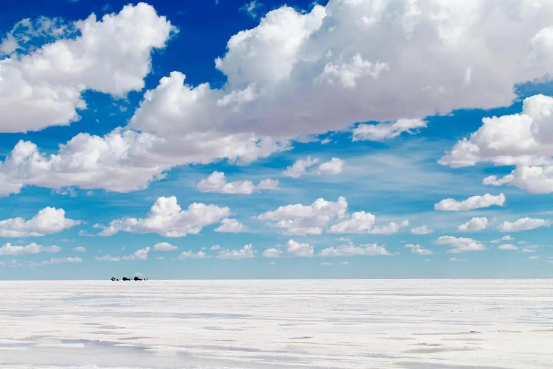 Three cars driving along the salar de uyuni under fluffy clouds