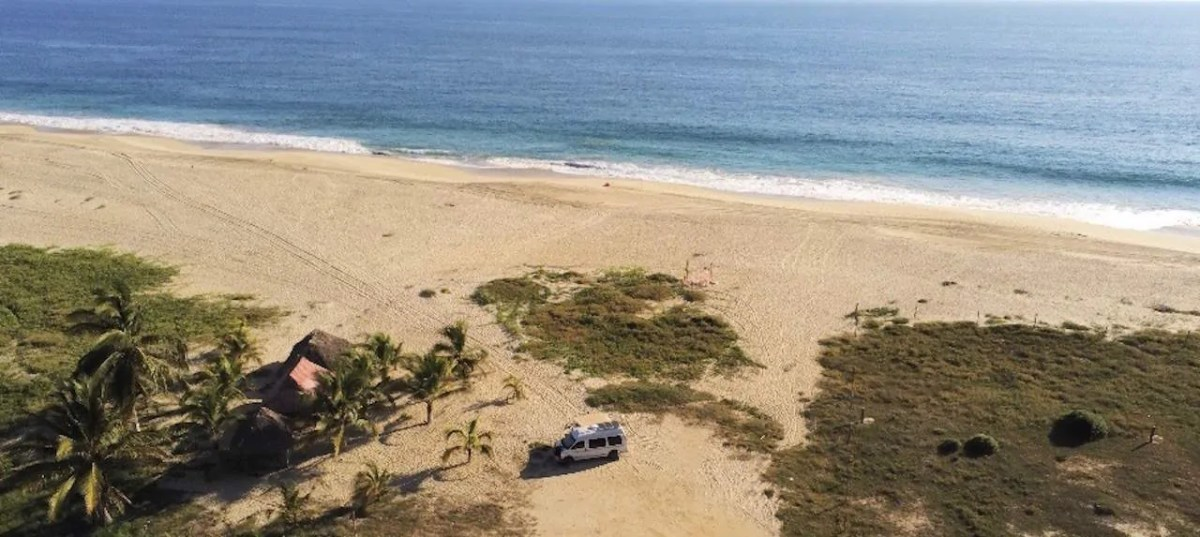 The van boondocking on an Isolated Beach Above Puerto Escondido. One of the best free campsites in Mexico.
