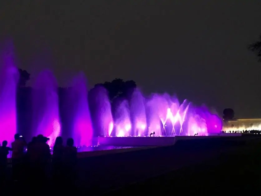 Fountains colored in pink and purple against the night sky at the Circuito Magico del Agua a staple on any one day trip in Lima