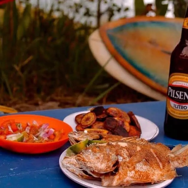 Fried whole fish with potatoes, a tomato cucumber salad and a beer