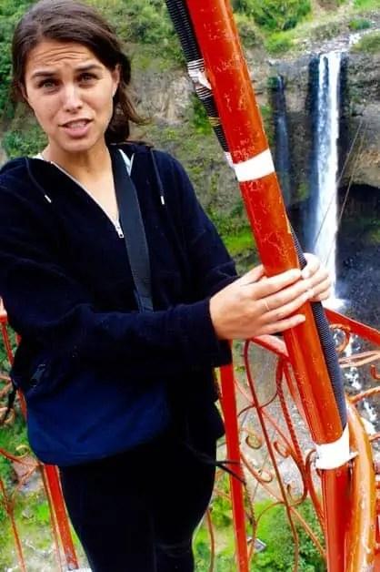 A girl on a tarabita in Banos over Rio Pastaza