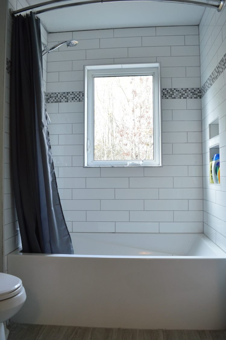 white subway tile shower with blue accent tile