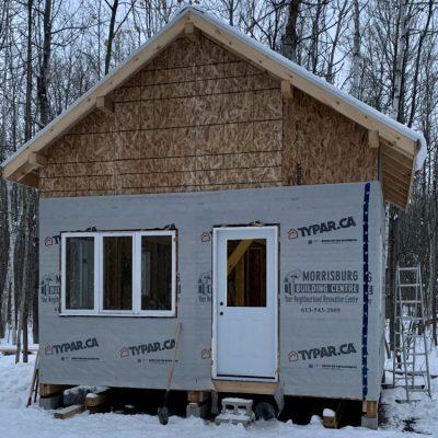 Phase 3: Housewrap, cabin windows, and exterior door