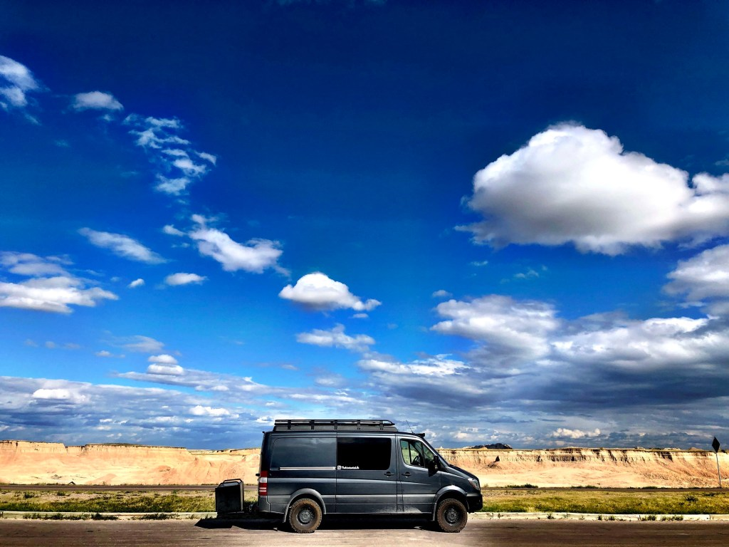 The Vantastic Life in Badlands National Park with blue sky and clouds