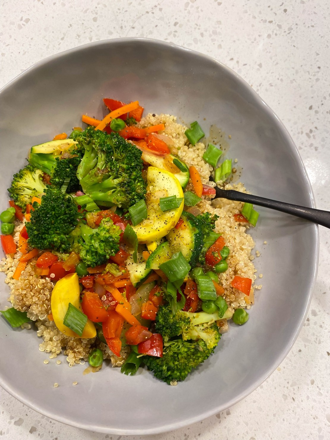 broccoli zucchini red bell pepper on top of cooked quinoa in gray bowl
