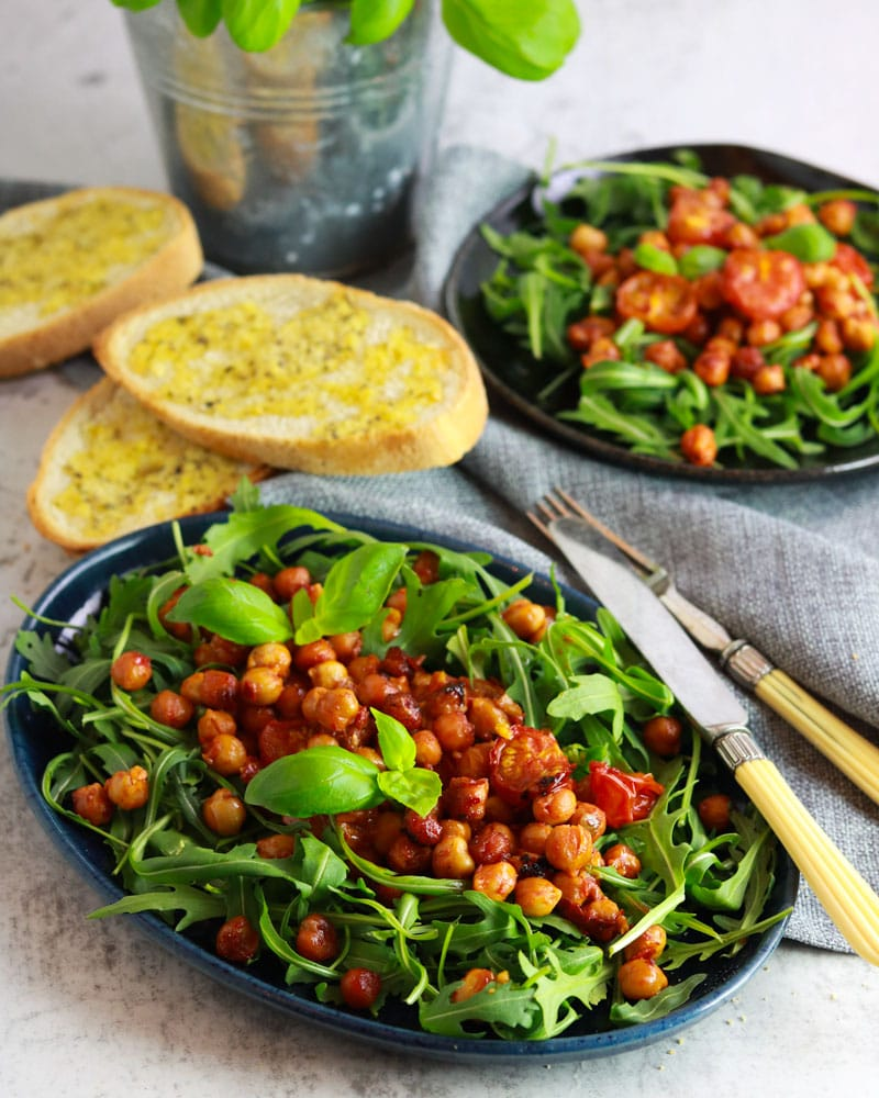 Harissa Roasted Chickpea & Tomato Salad on a plate with some garlic bread