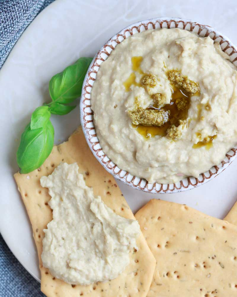 Cannellini and pesto dip on a plate with crackers