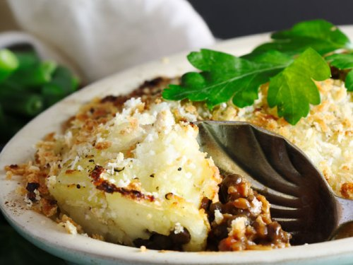 Vegan Shepherdess pie with a spoon serving it out