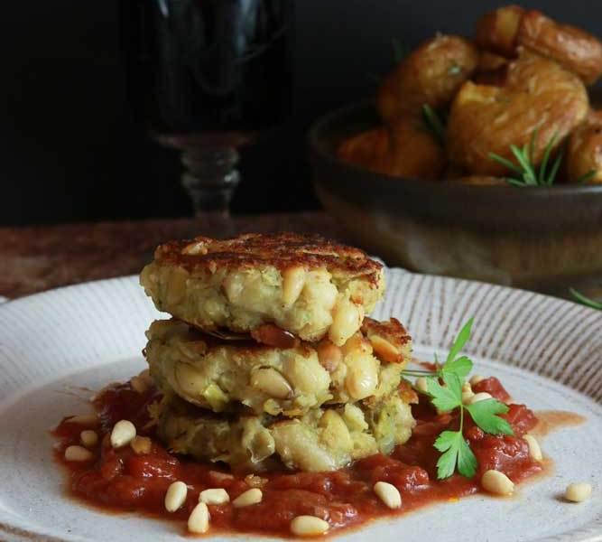vegan artichoke and cannelini crab cakes with wine and potatoes in the background