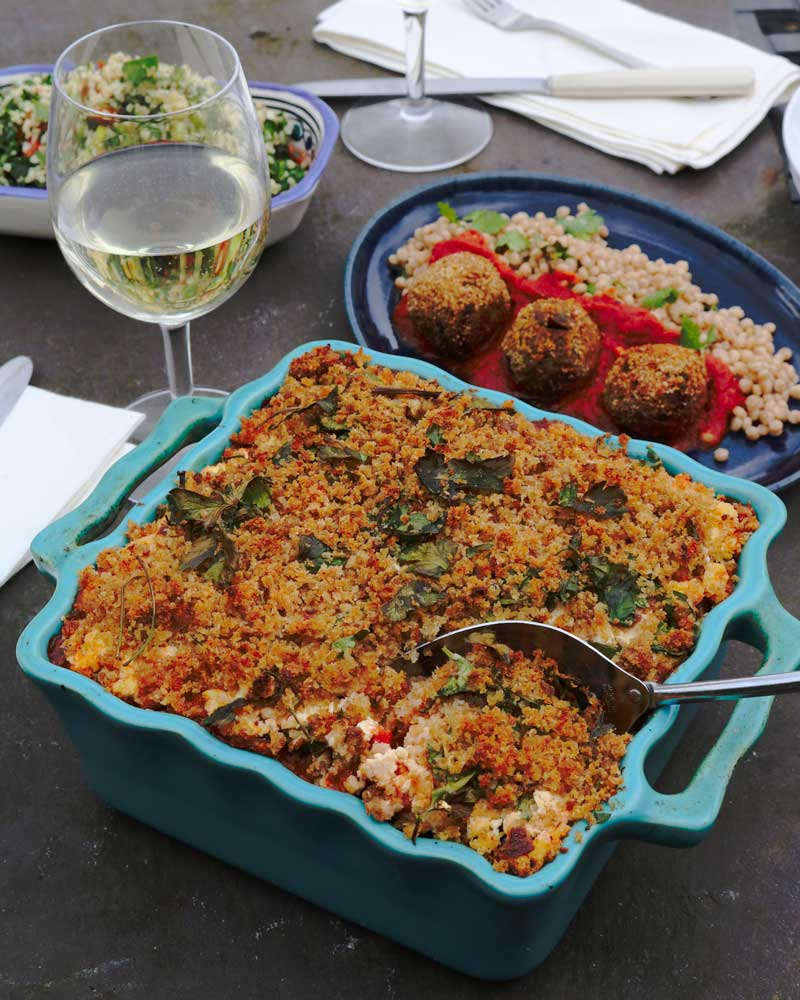 Vegan Greek Casserole with a spoon on a table with side dishes in the background