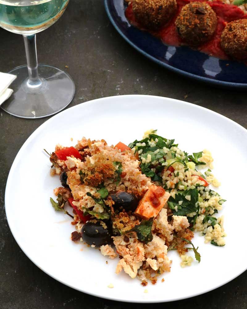 "Vegan ""feta"" casserole on a plate with tabbouleh salad."