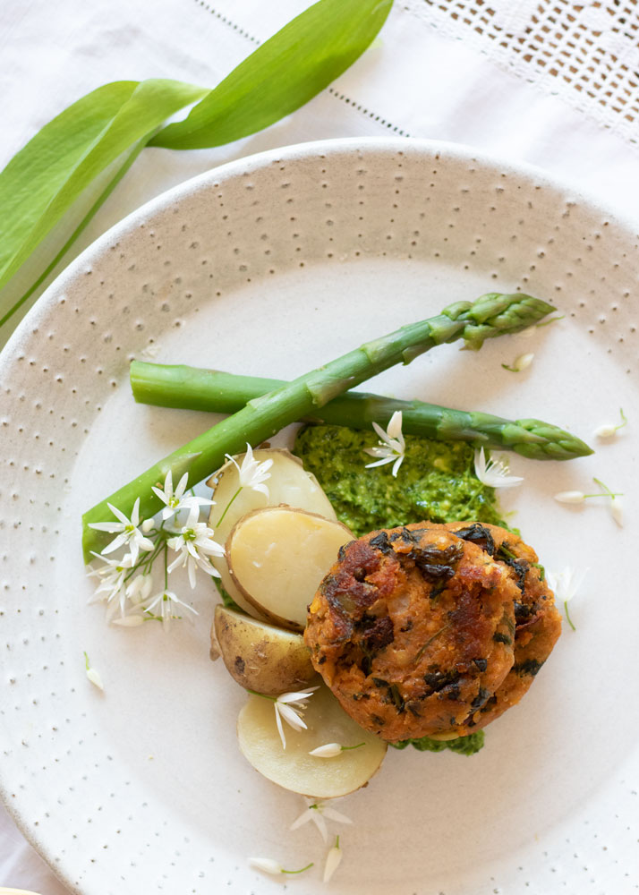 Herb Infused Lentil Cakes on a plate with Asparagus, potatoes and wild garlic pesto looking down from the top
