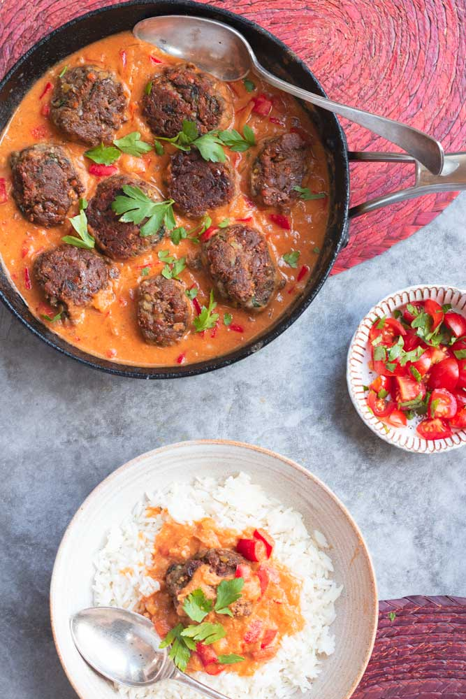Lentil Koftas in a pan with curry sauce. With a plate of lentil kofta, sauce and rice next to it.